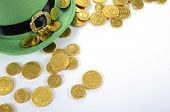 stock photo of pot gold  - Happy St Patricks Day leprechaun hat gold chocolate coins on white table - JPG