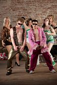stock photo of raunchy  - Raunchy dancing men with sunglasses at a 1970s Disco Music Party - JPG