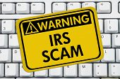 stock photo of irs  - IRS Scam Warning Sign A yellow sign with the words IRS Scam on a keyboard - JPG