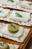 picture of brie cheese  - close up of slices of brie cheese on everything crackers with sliced of olives and fresh dill - JPG