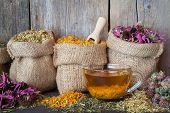 stock photo of tea bag  - Healing herbs in hessian bags and healthy tea cup herbal medicine - JPG