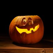 stock photo of jack-o-lantern  - Happy smiling jack o lantern Halloween pumpkin glowing from the inside and placed over the wooden boards surface - JPG