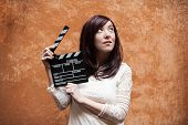 image of hippy  - Young woman in 70s hippie style closeup with clapperboard outdoor orange wall background - JPG