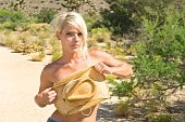 foto of implied nudity  - A blond woman hides her breasts with her cowboy hat - JPG