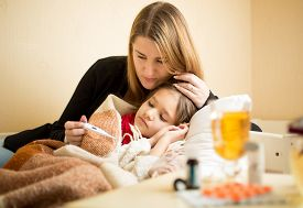 image of temperature  - Young mother checking temperature of sick daughter lying in bed - JPG