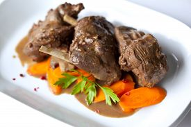stock photo of boar  - Wild boar stew and carrots on a plate - JPG