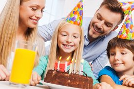 image of birthday hat  - Happy family of four celebrating birthday of happy little girl sitting at the table with birthday cake on it - JPG