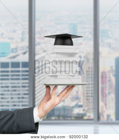 Student's Hand Is Holding A Gadget With Book And Graduation Hat On It. New York Panoramic View.