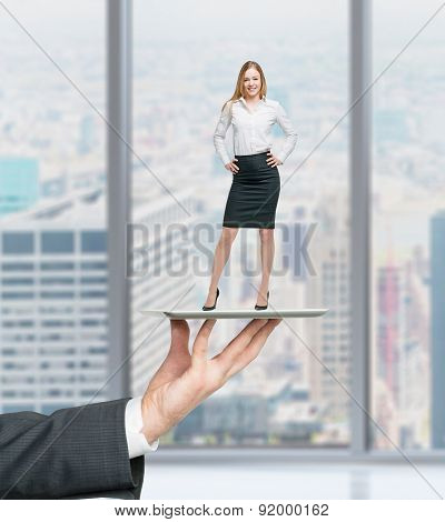 Businessman's Hand Is Holding A Gadget With Standing Beautiful Employee On It. Human Recourses Conce