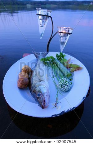 Fresh fish catch on a plate with vegetables above water by the lake in summer evening in Finland