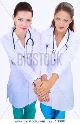 Young woman doctor stacking hands together over white background .