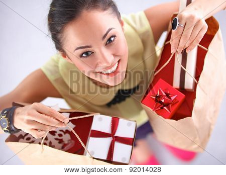Smiling woman with christmas gifts .