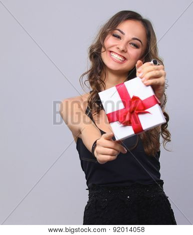 Young woman happy smile hold gift box in hands, isolated over grey