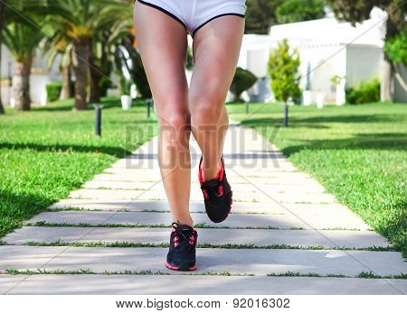 Runner Feet Running On Road In The Park. Woman Fitness Sunrise Jog Workout Welness Concept
