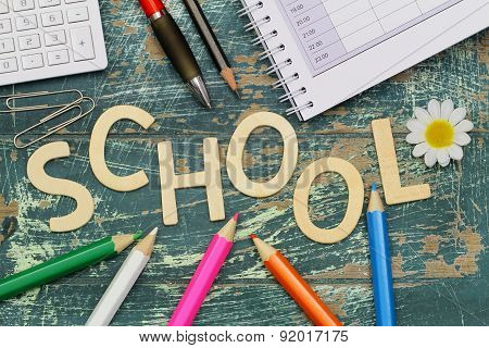 School written with wooden letters and school items on rustic wood