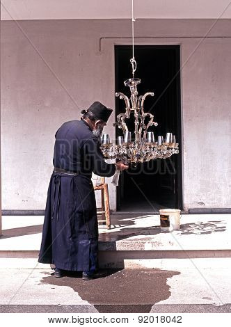 Monk cleaning light, Cyprus.
