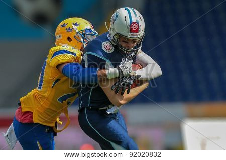 ST. POELTEN, AUSTRIA - JUNE 1, 2014: QB Miro Kadmiry (#7 Finland) is tackled by DB Philip Minja (#21 Sweden).