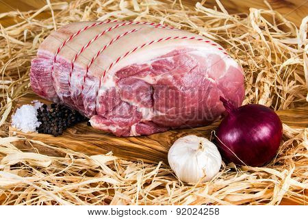 Farm British Boneless Pork Shoulder on cutting board and straw, onion, garlic, black pepper and Sea
