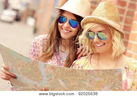 A picture of two girl friends sightseeing the city with a map