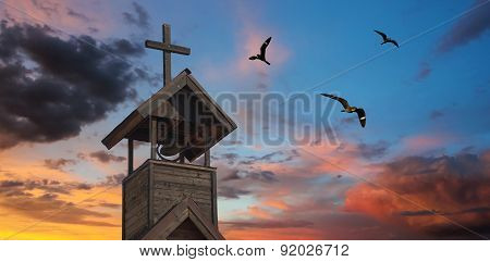 A Bell Tower With Cross And Nighthawks