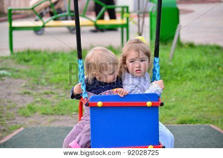 Two Little Girl On  Swing Ride