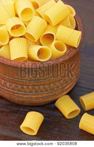 Macaroni italian pasta in wood bowl, on wood background
