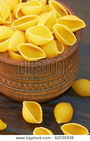Conchiglioni italian pasta in wood bowl, on wood background