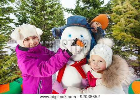 Close-up of happy children build cheerful snowman