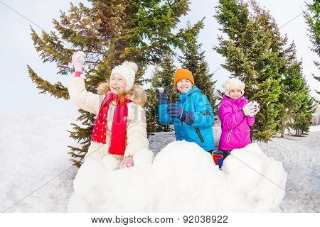 Group of children play snowballs game in forest