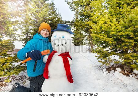 Boy holding carrot to put as nose of snowman