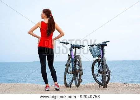 Sport woman with bicycles on the beach