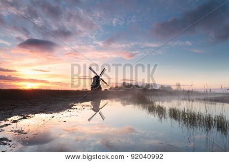 Windmill By River In Morning Mist