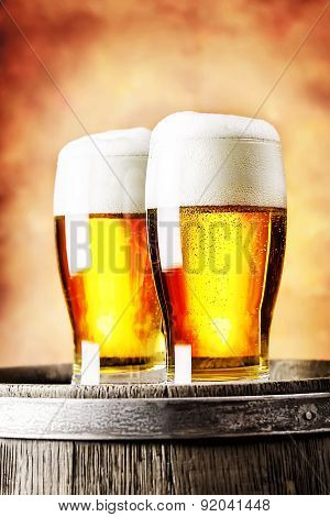 Two glasses of light beer standing on a wooden barrel