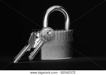 Padlock with keys on a black background