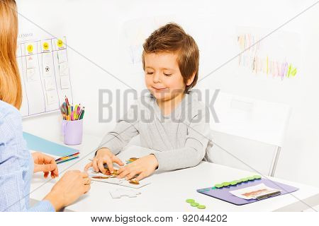 Smiling cute boy plays developing game with parent