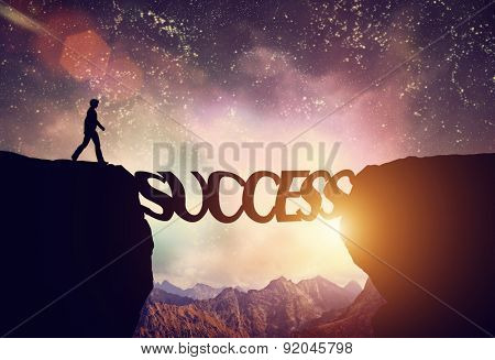 Man about to walk over precipice on SUCCESS word bridge. Dream sky and mountains. Motivation, ambition, business concept.