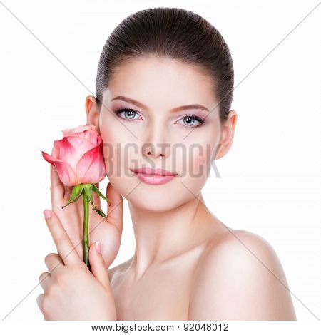 Beautiful young brunette woman with healthy skin and pink flowers near face - isolated on white.