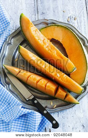 Cantaloupe Melon Slices On Metal Rustic Plate.