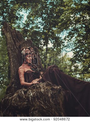 Nymph sitting on her throne in a magical forest