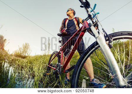 Young man with dirty clothes standing with his bicycle in the swamp