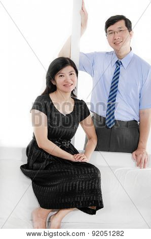 Couple Middle Aged relaxing in living room and smiling