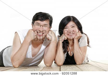 Portrait Of Middle Aged Couple lying down posing n wooden floor
