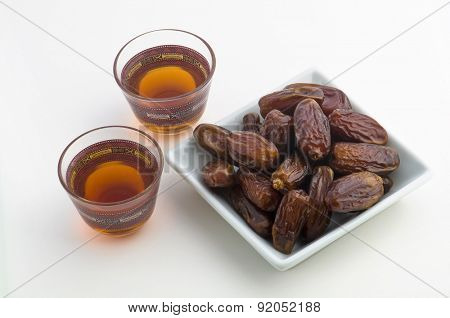 Black tea and Arabian dates on white background.
