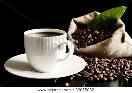 Cup Of Coffee With Bag And Coffee Beans With Green Leaf On Black