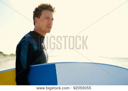 Young Surfer Standing On A Beach At Sunset