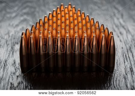 Macro shot of copper bullets that are in many rows to form a tri