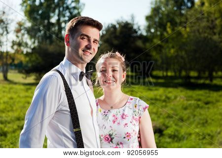 Young couple in love portrait in summer park. Woman in dress and man wearing shirt with braces and bow tie. Looking at the camera. Date, fiance with fiancee concepts