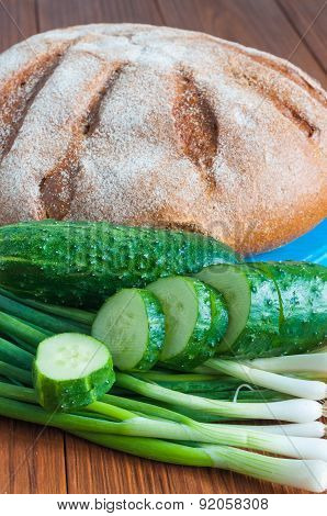 Freshly baked bread, cucumber and green onion in rural or rustic kitchen on vintage wood table from