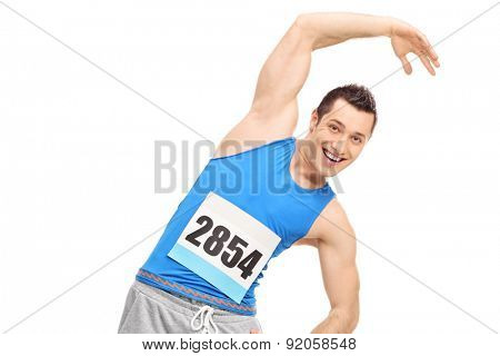 Young male runner in a blue tank top doing stretching exercise and looking at the camera isolated on white background