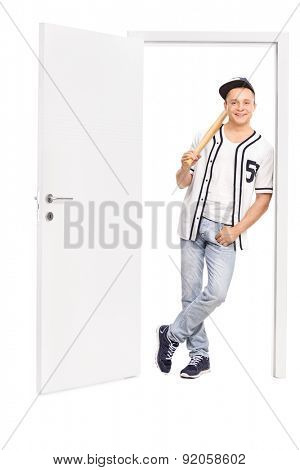 Full length portrait of a young baseball player holding a baseball bat and leaning on a frame of an open door isolated on white background
